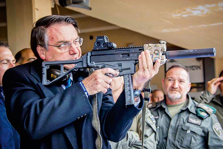 Bolsonaro segurando arma